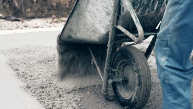 workers pouring concrete on the ground and distributing it - betonowy filmów i materiałów b-roll