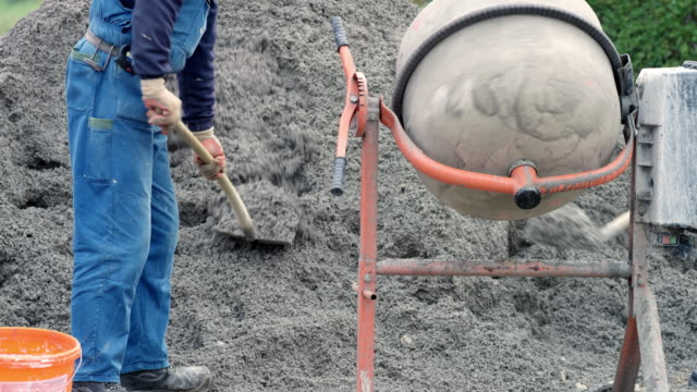 Workers putting sand into the concrete mixer