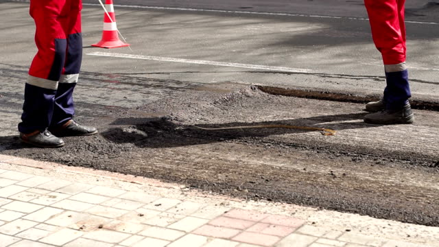 Workers remove shovels old cut asphalt from the road for laying new asphalt.