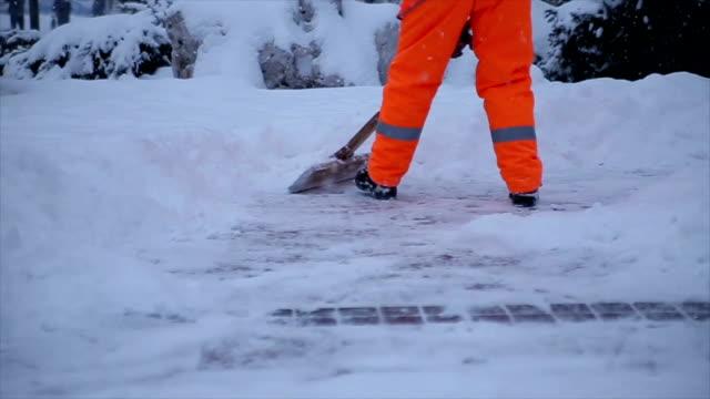 vidéos et rushes de travailleurs balayent la neige de la route en hiver. nettoyage de la ville de tempête de neige - uniforme