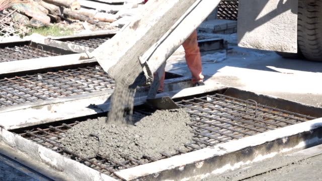 Workers take concrete from a mixer into a formwork Video of Workers take concrete from a mixer into a formwork civil engineering stock videos & royalty-free footage