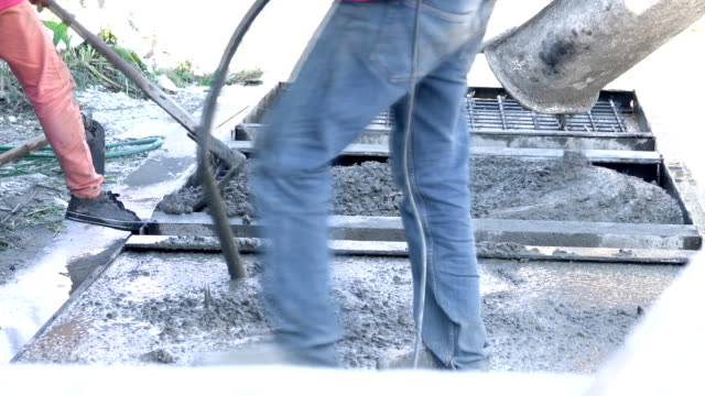 Workers take concrete from a mixer into formwork. Video Workers take concrete from a mixer into formwork. civil engineering stock videos & royalty-free footage