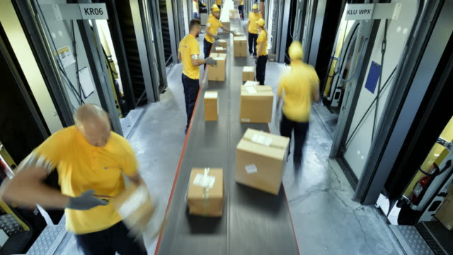 TIME-LAPSE Workers taking packages off the conveyor belt for further distribution
