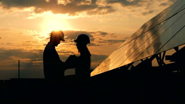 Workers talk near sun panels on a sunset background, side view. Engineers talking on a roof near solar panels. solar panels videos stock videos & royalty-free footage