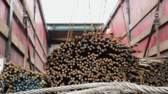 workers using a crane unload a bundle of steel rods - spranga video stock e b–roll