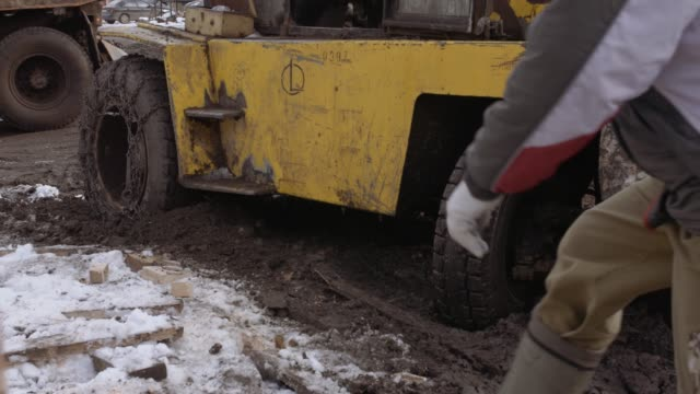 Workers walking in front of forklift stucked in deep mud video