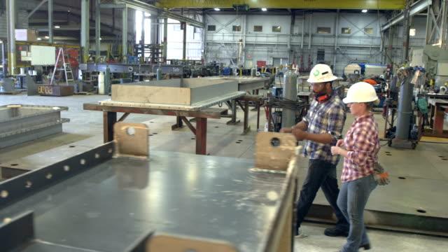 Workers walking through metal fabrication shop