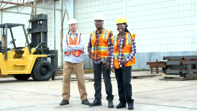 Workers wearing hardhats, safety vests and goggles