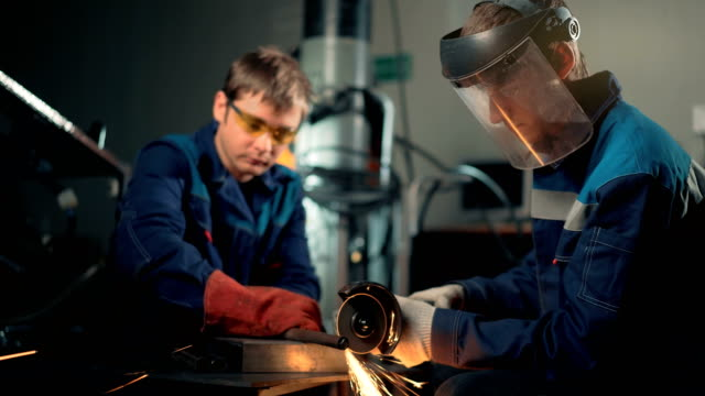 Workers wearing mask cuts metal with hand disc grinder abrasive saw Workers wearing mask cuts metal with hand disc grinder abrasive saw. metal worker stock videos & royalty-free footage