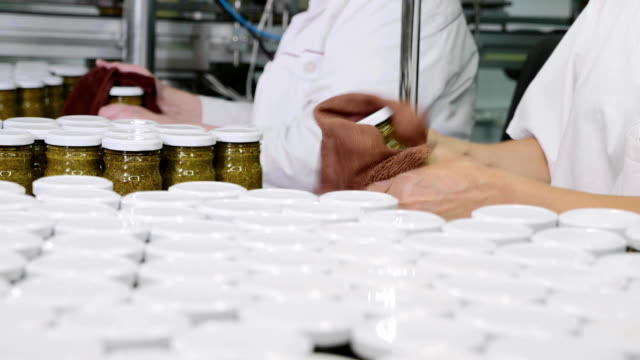 Workers wipes a glass jar with pesto sauce before branding at conveyor, close-up Workers wipes a glass jar with pesto sauce before branding at conveyor, close-up. Manual labor phase at sauce factory. pesto sauce stock videos & royalty-free footage
