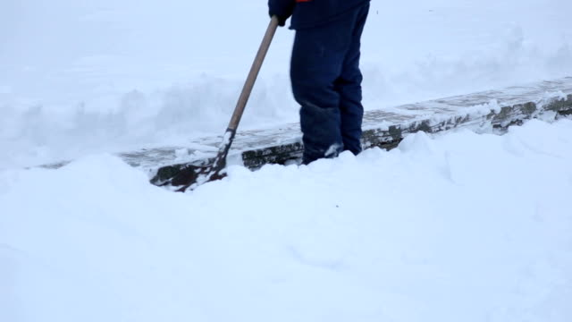 Workers with shovels to clear the snow from the stairs in the town square. Workers with shovels to clear the snow from the stairs in the town square. Workers sweep snow from road in winter, Cleaning road from snow storm. plow stock videos & royalty-free footage