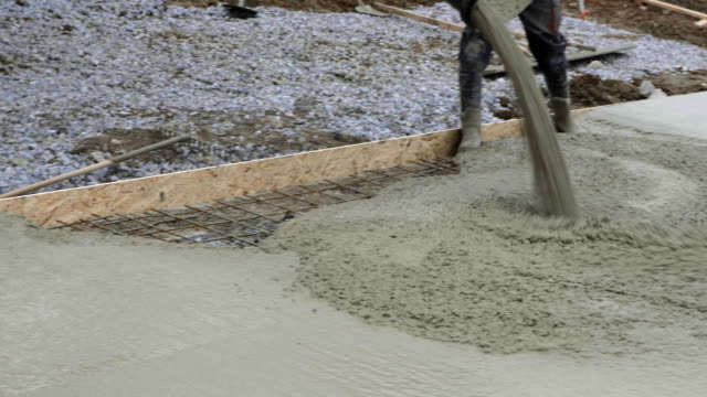 Workers work on site. Detail of casting pump concrete to foundations of family house video