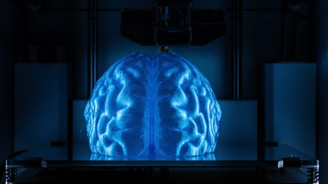 Working 3D printer, printing a human brain model symbolising artificial intelligence 4K Time Lapse Video of 3d printing process with plastic wire filament (PLA) in additive manufacturing technique.   PLA (Polylactide Acid)  is a biodegradable and bioactive thermoplastic aliphatic polyester derived from renewable resources, such as corn starch (in the United States and Canada), cassava roots, chips or starch (mostly in Asia), or sugarcane (in the rest of the world). In 2010, PLA had the second highest consumption volume of any bioplastic of the world. computer aided manufacturing stock videos & royalty-free footage