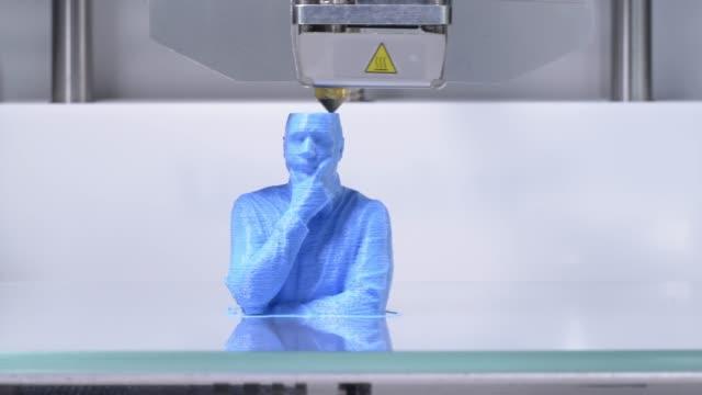 Impressora 3D, imprimindo uma série de bustos de humanos - símbolo para a inteligência artificial a trabalhar - vídeo