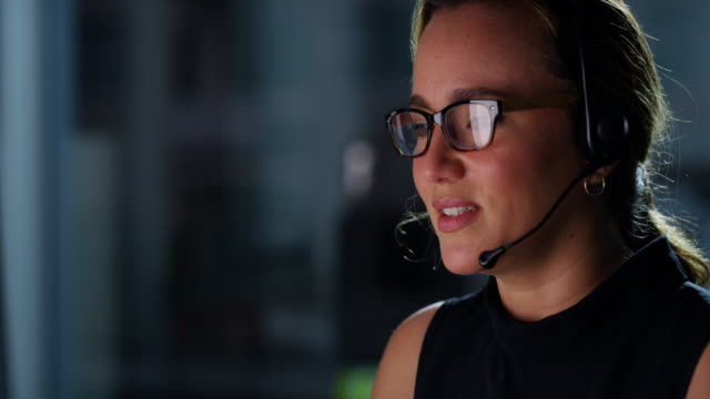 Working around the clock to care for customers 4k video footage of a young woman using a computer and headset at night in a modern office call center stock videos & royalty-free footage