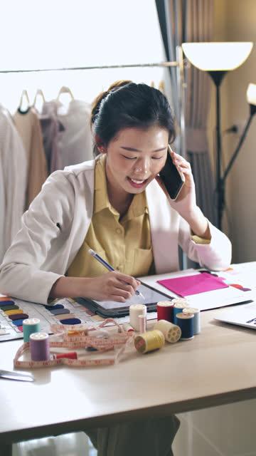 vídeos y material grabado en eventos de stock de trabajando diseñador de moda asiático hablando por teléfono con su cliente para la solución de diseñador, vertical - bocetos de diseños de moda