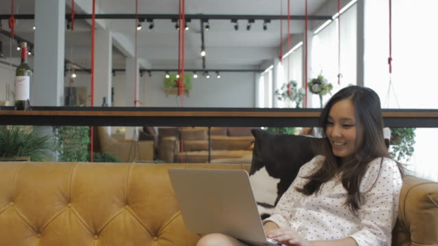 在宅で自宅のソファの上の作業の概念: 東南アジアの女の子 ビデオ