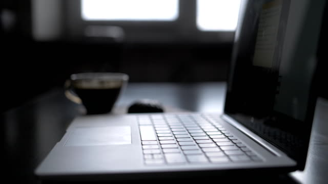Working at night, a laptop and a cup of hot coffee evaporation on a table video