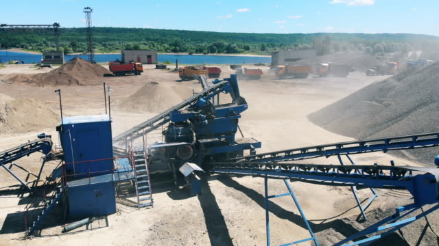 Working conveyor moves crushed stone at a quarry. Mining industry equipment.