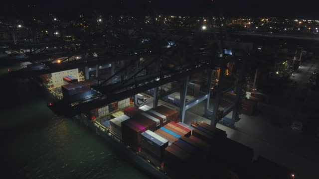 vídeos de stock e filmes b-roll de working crane and container ship in industrial port at night, aerial video - drone shipyard night