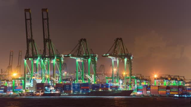 夜の工業港で働くクレーンおよびコンテナ船、シンガポール、タイムラプスビデオ ビデオ