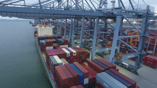 arbetskran och containerfartyg i hamnen i skymning, international cargo port, aerial video - skrov bildbanksvideor och videomaterial från bakom kulisserna