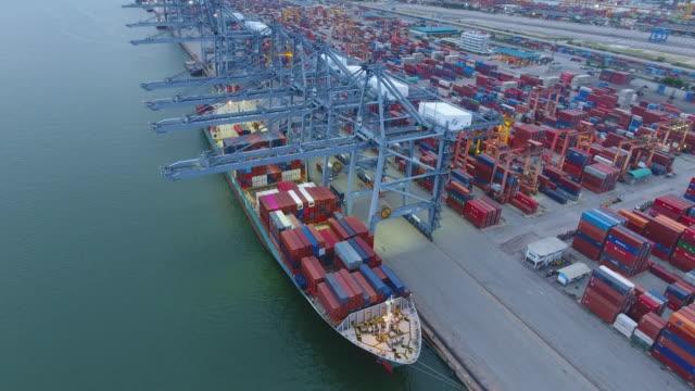 working crane and container ship i hamnen vid skymningen, international cargo port, aerial video - skrov bildbanksvideor och videomaterial från bakom kulisserna
