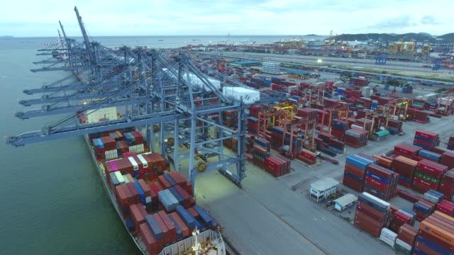 working crane on container ship in industrial port, aerial video - ludzka osada filmów i materiałów b-roll