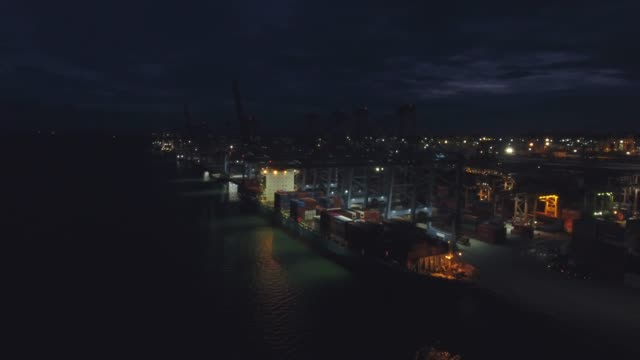 vídeos de stock e filmes b-roll de working crane on container ship in industrial port at night, aerial video - drone shipyard night