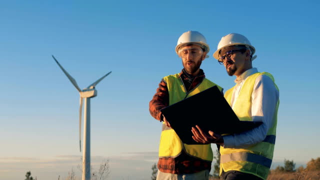 working engineers look at a laptop in hands. environmental energy concept. - efficacia video stock e b–roll