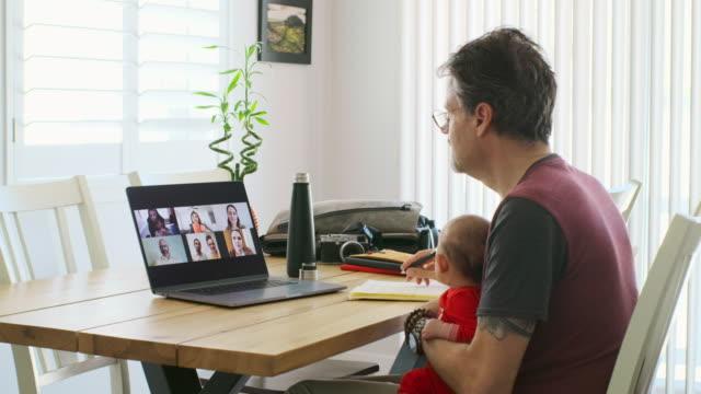 vídeos de stock e filmes b-roll de working father at home on a web chat meeting - envolvimento dos funcionários