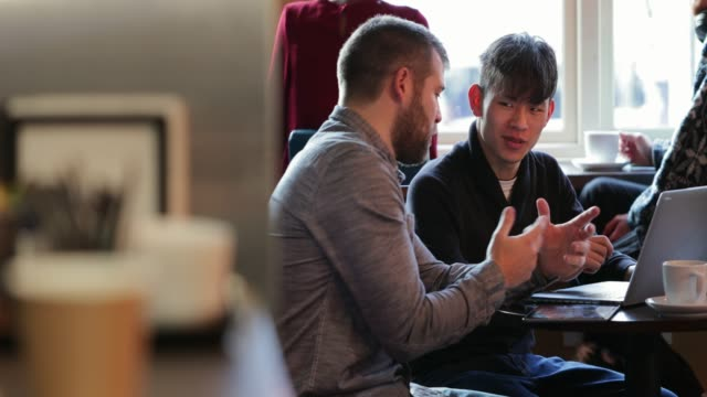 Working in an Internet Cafe Panning view of two male friends sitting in a cafe. They are using a laptop while sitting at a table, working on the go. small business saturday stock videos & royalty-free footage
