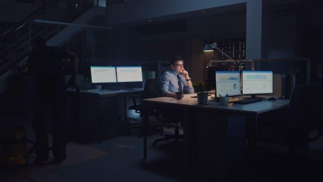 vídeos y material grabado en eventos de stock de trabajando tarde en la noche en la oficina: empresario utiliza computadora de escritorio, analizando, utilizando documentos, resolviendo problemas, terminando proyecto importante. diligente joven trabajador ambicioso. limpieza hombre vacuums piso - urgencia