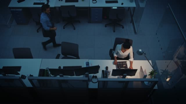 Working Late at Night in the Office: Businesswoman Using Desktop Computer, Analyzing, Using Documents, Solving Problems, Finishing Project. Colleague Says Goodbye and Leaves. Elevated High Angle Shot