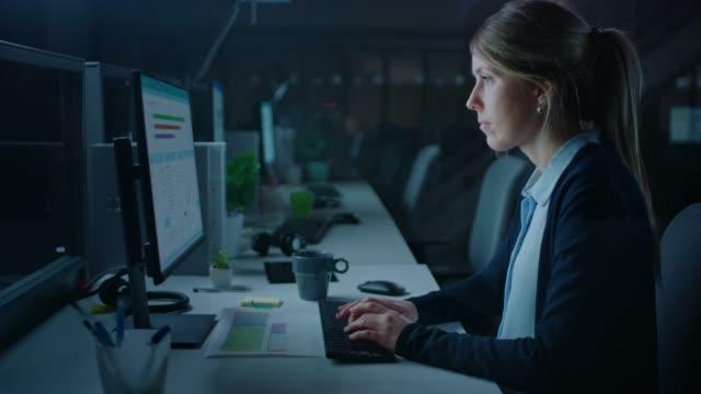 arbeiten ende der nacht im büro: geschäftsfrau nutzt desktop-computer, analysieren, dokumente nutzen, probleme lösen, finishing-projekt abschließen. - verantwortung stock-videos und b-roll-filmmaterial