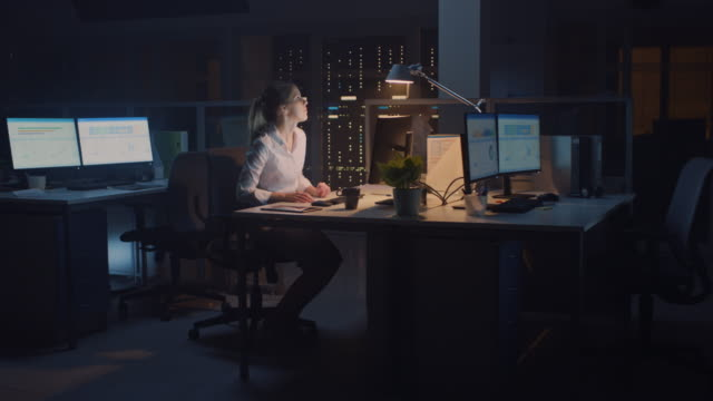 working late at night in the office: businesswoman using desktop computer, analyzing, using documents, solving problems, after finishing project she stands up turns off the light and leaves - odejście filmów i materiałów b-roll