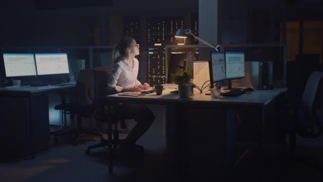 vídeos y material grabado en eventos de stock de trabajando tarde en la noche en la oficina: empresaria usando computadora de escritorio, analizando, usando documentos, resolviendo problemas, después de terminar el proyecto ella se levanta apaga la luz y deja - despedida