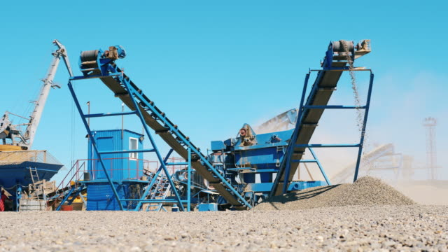 Working machine crushes stones into rubble at a quarry. Mining industry concept.