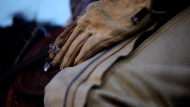 рабочий человек на лошади держа сигарету в кожаные перчатки - скаковая лошадь стоковые видео и кадры b-roll