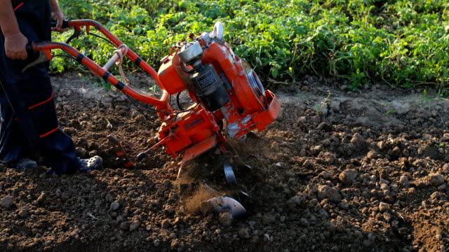 Working man with motor cultivator Farmer working in the field. Spring work on the farm. Man plowing the garden harrow agricultural equipment stock videos & royalty-free footage
