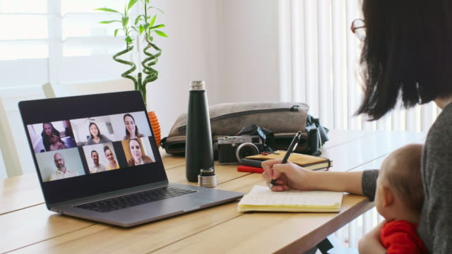 Working Mother at Home on a Web Chat Meeting A working mother at home participating in a online web meeting. zoom call stock videos & royalty-free footage