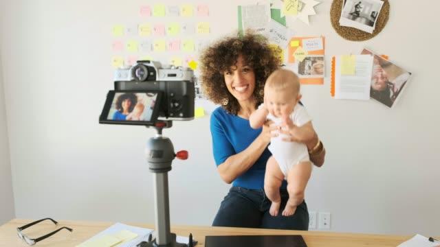 arbeitende mutter balanciert baby-und designarbeit - bloggen stock-videos und b-roll-filmmaterial
