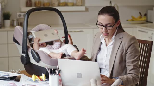 Mère de travail divertissant le bébé avec l'ordinateur de tablette - Vidéo