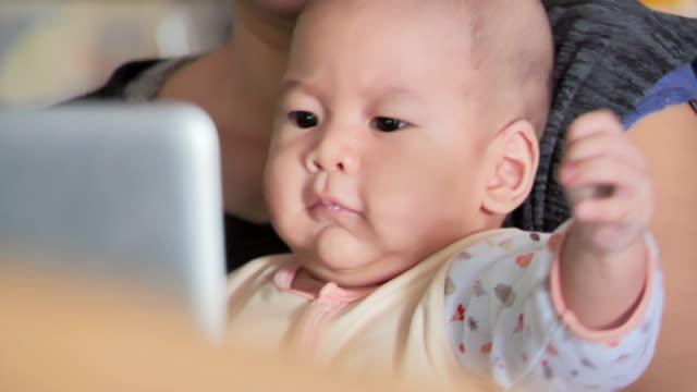 arbetande mamma med baby vid bordet. upptagen kvinna som arbetar på laptop med baby på händer. kvinnliga frilansuppdrag. modern moderskapet. millennial föräldrar, teknologi, utbildning - working from home bildbanksvideor och videomaterial från bakom kulisserna