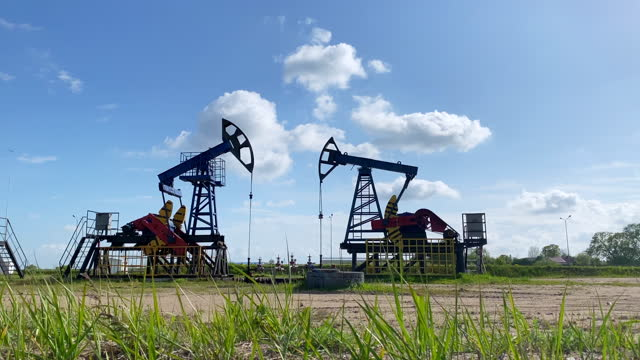 Working oil pumps from an oil field. Industrial equipment. Oil production. Silhouette.