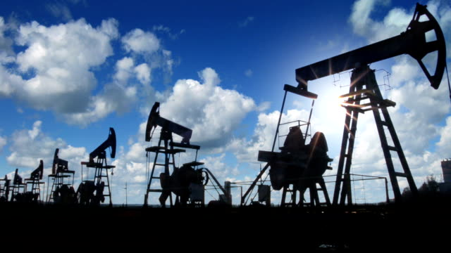 working oil pumps silhouette against timelapse clouds video
