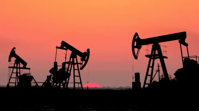 working oil pumps silhouette against timelapse sunrise video