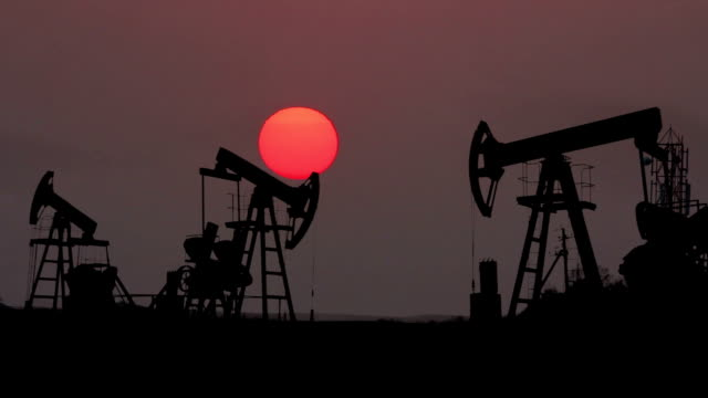 working oil pumps silhouette against timelapse sunset video