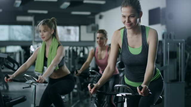 Working Out on Stationary Bikes Cycling Together in exercise class exercise bike stock videos & royalty-free footage