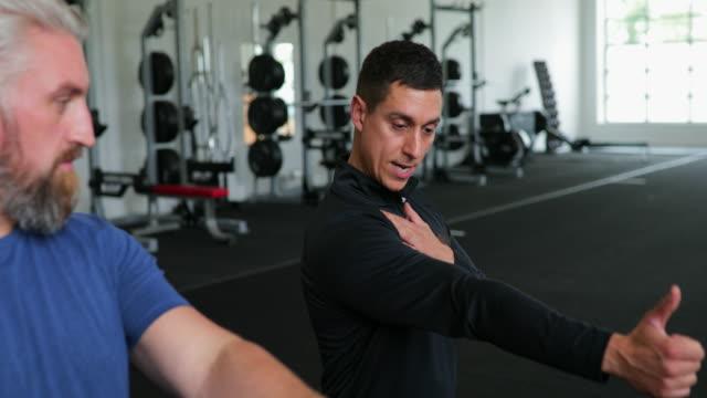 vídeos de stock, filmes e b-roll de malhando com a ajuda de um personal trainer - personal trainer